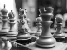 Το χέρι χάρασε, ξύλινα κομμάτια σκακιού που είδαν σε έναν πίνακα σκακιού πληγών ανταγωνισμού Στοκ φωτογραφίες με δικαίωμα ελεύθερης χρήσης