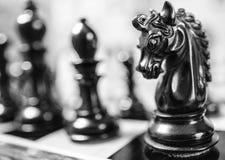 Το χέρι χάρασε, ξύλινα κομμάτια σκακιού που είδαν σε έναν πίνακα σκακιού πληγών ανταγωνισμού Στοκ Εικόνες