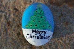 Το χέρι Χαρούμενα Χριστούγεννας χρωμάτισε το μικρό βράχο Στοκ Φωτογραφία
