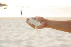 Το χέρι χύνει την άμμο στοκ εικόνες