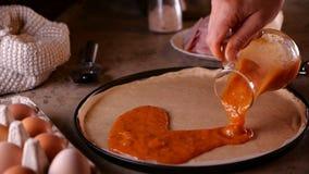 Το χέρι χύνει τη σάλτσα πιτσών στη ζύμη στο τηγάνι ψησίματος - κινηματογράφηση σε πρώτο πλάνο, σε αργή κίνηση φιλμ μικρού μήκους
