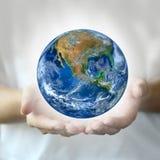 Το χέρι δύο κρατά τη γη, συμπεριλαμβανομένων των στοιχείων που εφοδιάζονται από τη NASA Στοκ Εικόνα