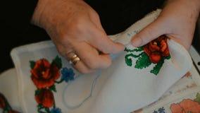 Το χέρι Grandma κεντά μια διαγώνιος-βελονιά φιλμ μικρού μήκους