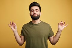 Το χαλαρωμένο ξένοιαστο άτομο προσπαθεί να χαλαρώσει μετά από τη σκληρή εργάσιμη ημέρα, μεσολαβεί και κλείνει τα μάτια, απολαμβάν στοκ εικόνα