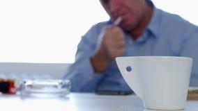 Το χαλαρωμένο πρόσωπο καπνιστών στο εσωτερικό γραφείο παίρνει και ανάβει ένα τσιγάρο από ένα πακέτο φιλμ μικρού μήκους