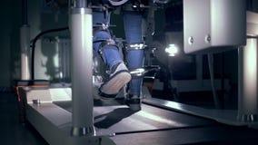 Το χαμηλότερο σώμα ενός ασθενή παίρνει εκπαιδευμένο σε μια μηχανή προσομοίωσης περπατήματος απόθεμα βίντεο