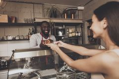 Το χαμογελώντας άτομο barista δίνει σε ένα κορίτσι τη διαταγή της στοκ εικόνες