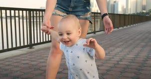 Το χαμογελώντας αγόρι που κρατά το χέρι της μητέρας του κάνει τα πρώτα βήματα περπατώντας κατά μήκος του περιπάτου το καλοκαίρι φιλμ μικρού μήκους