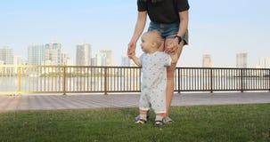 Το χαμογελώντας αγόρι που κρατά το χέρι της μητέρας του κάνει τα πρώτα βήματα περπατώντας κατά μήκος του περιπάτου το καλοκαίρι απόθεμα βίντεο