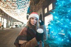 Το χαμογελώντας γλυκό κορίτσι σε ένα καπέλο Χριστουγέννων και ένα φλιτζάνι του καφέ στα χέρια της στέκεται στοκ φωτογραφίες με δικαίωμα ελεύθερης χρήσης