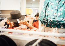 Το χαμογελώντας θηλυκό προσπαθεί στο νέο καπέλο εξετάζει την αντανάκλαση καθρεφτών 2 στοκ φωτογραφίες