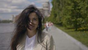 Το χαμογελώντας κορίτσι αγγίζει επάνω την τρίχα της απόθεμα βίντεο
