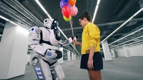 Το χαμογελώντας κορίτσι δίνει τα ζωηρόχρωμα μπαλόνια σε ένα cyborg απόθεμα βίντεο