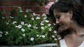 Το χαμογελώντας κορίτσι κοιτάζει και αγγίζει μια ανθοδέσμη των λουλουδιών Πορτρέτο μιας χαριτωμένης ελκυστικής γυναίκας απόθεμα βίντεο
