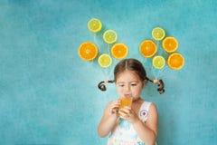 Το χαμογελώντας κορίτσι πίνει το φρέσκο χυμό από πορτοκάλι Στοκ Φωτογραφίες