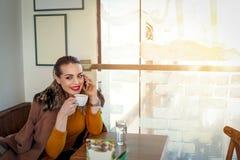 Το χαμογελώντας κορίτσι σε έναν καφέ πίνει τον καφέ και την ομιλία στο smartphone Στοκ φωτογραφία με δικαίωμα ελεύθερης χρήσης