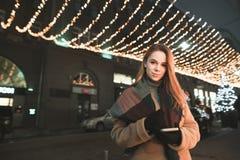 Το χαμογελώντας κορίτσι σε ένα παλτό και ένα smartphone στα χέρια του στέκεται στο υπόβαθρο των διακοσμήσεων φωτεινών σηματοδοτών στοκ εικόνες