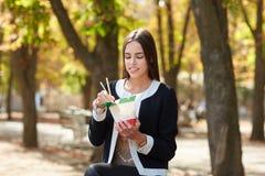 Το χαμογελώντας κορίτσι brunette εξετάζει το κινεζικό αυγό noodless στο πάρκο στο υπόβαθρο φύσης Στοκ Εικόνες