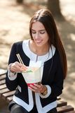 Το χαμογελώντας κορίτσι brunette εξετάζει το κινεζικό αυγό noodless στο πάρκο στο υπόβαθρο φύσης Στοκ φωτογραφίες με δικαίωμα ελεύθερης χρήσης