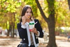 Το χαμογελώντας κορίτσι brunette εξετάζει το κινεζικό αυγό noodless στο πάρκο στο υπόβαθρο φύσης Στοκ φωτογραφία με δικαίωμα ελεύθερης χρήσης