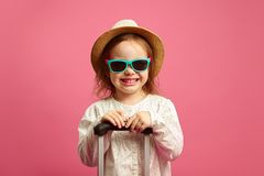 Το χαμογελώντας μικρό κορίτσι στα γυαλιά ηλίου και το καπέλο αχύρου, που κρατά τη βαλίτσα στο απομονωμένο ροζ, εκφράζει ειλικρινά στοκ φωτογραφία