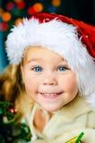 Το χαμογελώντας παιδί στο καπέλο Santa έχει Χριστούγεννα Στοκ εικόνα με δικαίωμα ελεύθερης χρήσης