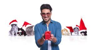 Το χαμογελώντας περιστασιακό άτομο προσφέρει το χριστουγεννιάτικο δώρο με το behi γατών santa στοκ φωτογραφία με δικαίωμα ελεύθερης χρήσης