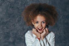 Το χαμογελώντας όμορφο κορίτσι με τη σγουρή τρίχα κρατά τα χέρια κοντά στο πρόσωπο και είναι ευχαριστημένο στοκ εικόνες