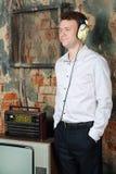 Το χαμογελώντας άτομο στα μεγάλα ακουστικά ακούει παλαιό ραδιόφωνο Στοκ Φωτογραφίες