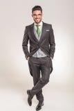 Το χαμογελώντας επιχειρησιακό άτομο που στέκεται με δικούς του παραδίδει τις τσέπες Στοκ Εικόνα
