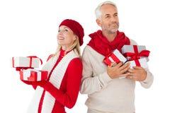 Το χαμογελώντας ζεύγος στην εκμετάλλευση χειμερινής μόδας παρουσιάζει Στοκ εικόνα με δικαίωμα ελεύθερης χρήσης