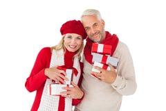 Το χαμογελώντας ζεύγος στην εκμετάλλευση χειμερινής μόδας παρουσιάζει Στοκ Φωτογραφίες
