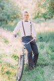 Το χαμογελώντας καλύτερο άτομο στο σύγχρονο μπλε κοστούμι κάθεται στο ποδήλατο στο πράσινο ηλιόλουστο δάσος Στοκ φωτογραφία με δικαίωμα ελεύθερης χρήσης