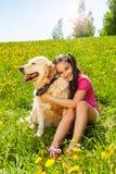 Το χαμογελώντας κορίτσι αγκαλιάζει τη χαριτωμένη συνεδρίαση σκυλιών στη χλόη Στοκ φωτογραφία με δικαίωμα ελεύθερης χρήσης