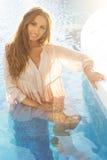 Το χαμογελώντας κορίτσι κάθεται στην πισίνα πέρα από τον ήλιο Στοκ φωτογραφία με δικαίωμα ελεύθερης χρήσης
