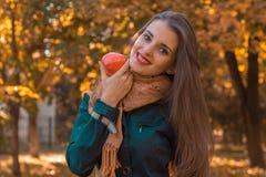 Το χαμογελώντας κορίτσι με την όμορφη τρίχα κρατά στο χέρι της Apple που κάμπτει το κεφάλι Στοκ φωτογραφία με δικαίωμα ελεύθερης χρήσης