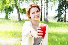 Το χαμογελώντας κορίτσι πίνει το χυμό Στοκ φωτογραφία με δικαίωμα ελεύθερης χρήσης