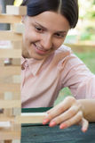 Το χαμογελώντας κορίτσι παίζει ένα ξύλινο παιχνίδι φραγμών στο πάρκο Στοκ φωτογραφία με δικαίωμα ελεύθερης χρήσης