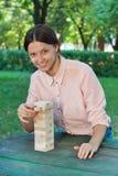 Το χαμογελώντας κορίτσι παίζει ένα ξύλινο παιχνίδι φραγμών Στοκ Φωτογραφίες