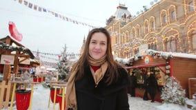 Το χαμογελώντας κορίτσι στέλνει τα φιλιά που στέκονται το χειμώνα στην κόκκινη πλατεία στη Μόσχα, μπροστά από τη ΓΟΜΜΑ κρατικών π απόθεμα βίντεο