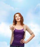 Το χαμογελώντας κορίτσι στην παρουσίαση περιστασιακών ενδυμάτων φυλλομετρεί επάνω Στοκ Φωτογραφία