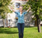 Το χαμογελώντας κορίτσι στην παρουσίαση περιστασιακών ενδυμάτων φυλλομετρεί επάνω Στοκ Φωτογραφίες
