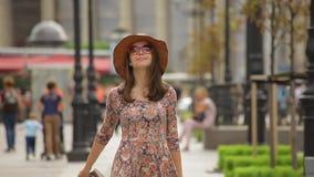 Το χαμογελώντας κορίτσι τουριστών με μια κυλώντας τσάντα αποσκευών κρατά έναν χάρτη και πηγαίνει προς τα εμπρός σε μια πόλη απόθεμα βίντεο