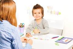 Το χαμογελώντας μικρό αγόρι κρατά το μολύβι και γεμίζει τις μορφές στοκ εικόνες με δικαίωμα ελεύθερης χρήσης