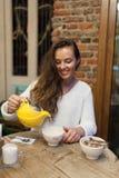 Το χαμογελώντας νέο κορίτσι στο εστιατόριο χύνει το πράσινο τσάι από κίτρινο teapot σε ένα φλυτζάνι Εστίαση σε μια κούπα του τσαγ Στοκ φωτογραφίες με δικαίωμα ελεύθερης χρήσης