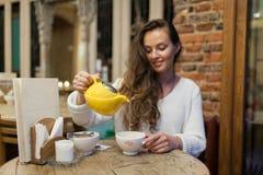 Το χαμογελώντας νέο κορίτσι στο εστιατόριο χύνει το πράσινο τσάι από κίτρινο teapot σε ένα φλυτζάνι Εστίαση σε μια κούπα του τσαγ Στοκ Εικόνα