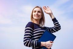 Το χαμογελώντας νέο όμορφο ξανθό κορίτσι με την ψηφιακή ταμπλέτα στα χέρια περιμένει το φίλο που κυματίζει το ένα χέρι κοντά στον Στοκ εικόνα με δικαίωμα ελεύθερης χρήσης