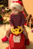 Το χαμογελώντας παιδί στο καπέλο Santa κάθεται σε ένα αυτοκίνητο μωρών Στοκ Φωτογραφία