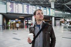 Το χαμογελώντας στοχαστικό άτομο μπροστά από τις αφίξεις και οι αναχωρήσεις επιβιβάζονται στον αερολιμένα με έναν καφέ Στοκ εικόνα με δικαίωμα ελεύθερης χρήσης