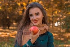 Το χαμογελώντας όμορφο κορίτσι στέκεται στο πάρκο και κρατά την κόκκινη Apple διαθέσιμη Στοκ Εικόνα